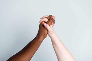Closeup photo of two hands arms different race multinational couple best friends anti racism issue help support together love save world romantic date isolated grey color background