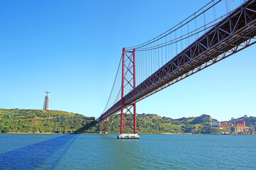 Photo sur Plexiglas Ponts 25 de Abril suspension Bridge connecting the city of Lisbon, to Almada & the statue of Christ in the background standing high above the southern banks of the Tejo Estuary, Lisbon, Portugal.