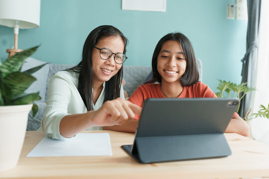 Asian family with daughter do homework by using tablet with mother help.