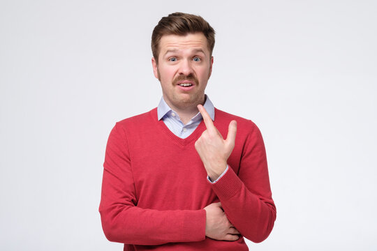 puzzled man indicates at himself with wondered expression, asks who me