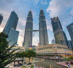 Kuala Lumpur, Malaysia - March 14, 2016: Petronas TwinTowers and Suria KLCC shopping mall at sunset, Kuala Lumpur, Malaysia on March 14, 2016.