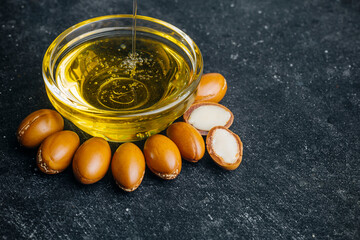 Argan seeds and oil on a dark wooden background. Argan oil based cosmetics concept.