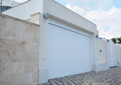 A close-up on a modern garage for cars with white garage door and lightning lamps.
