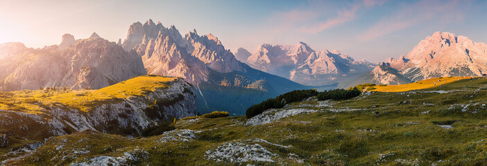 Fotomurales - Wonderful Alpine highlands during sunrise. Morning panoramic view of Dololites mountains, Italian Dolomites Alps under sunlight. Awesome landscape with colorful sky over the Cadini di Misurina range.