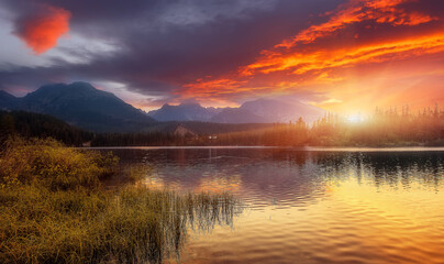 Fotomurales - Beautiful Autumn Landscape. Majestic Sunset on Strbske Pleso lake. Colorful morning view of High Tatra, Slovakia, Europe. Amazing Nature background. Wonderful Picturesque Scene. Picture of wild area