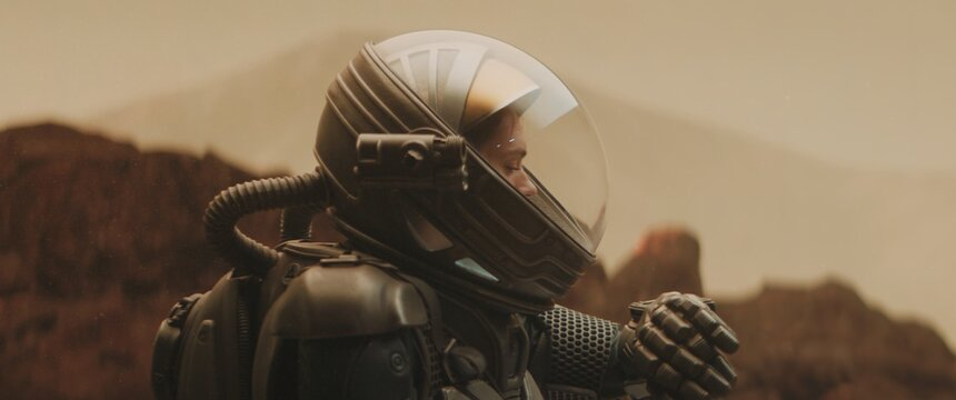 Caucasian female astronaunt checking hud on her suit while exploring planet surface, Mars colonization concept