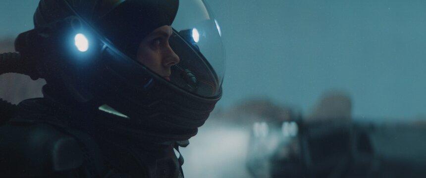 Caucasian female astronaunt wearing a space suit exploring planet surface, night shot