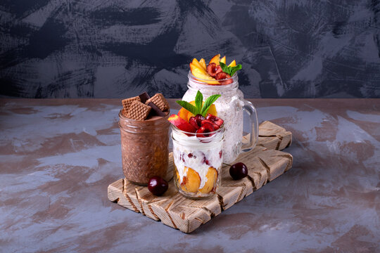 Overnight oats assortment in glass jars on the wooden board