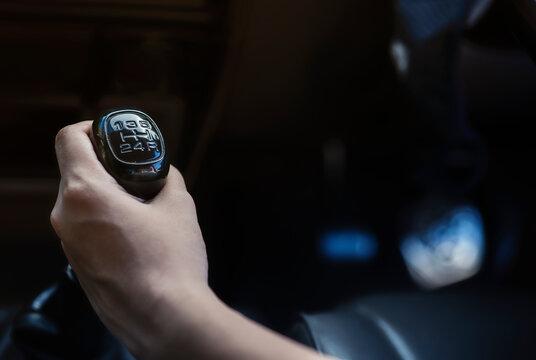 Driver hand shifting gear shift knob manually