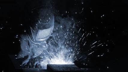 The welder at the factory is engaged in the production of metal structures.