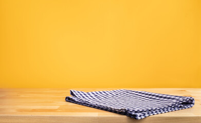 Blue fabric,cloth on wood table top on yellow wall background.