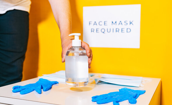Woman reopening her small business with the measures of social distancing, face mask, disinfectant gel and latex gloves to prepare the reopening and adaptation of the schools for the new normal.