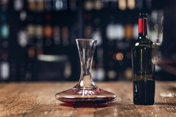 Red wine in bottle and decanter stands on wooden table in restaurant, dark background