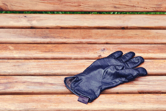 Forgotten leather wet glove on a park bench