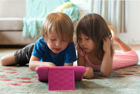 A little boy and girl watching tv on the tablet at home. Learning games and videos.
