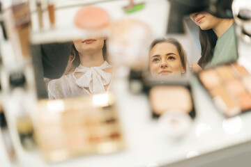 Close-up of faces of young woman and two female makeup artistes reflecting in mirror of powder on...