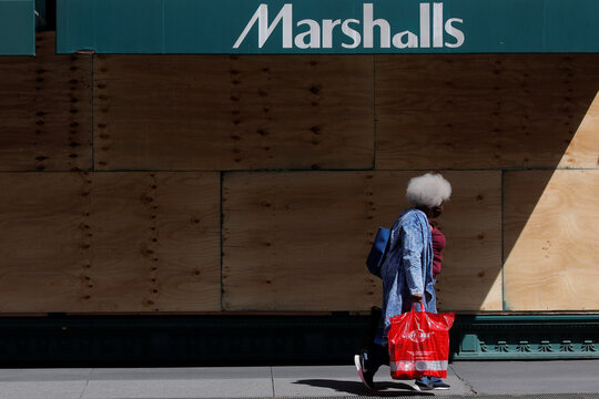 A woman walks with a shopping bag outside a Marshalls store, as phase one of reopening after lockdown begins, during the outbreak of the coronavirus disease (COVID-19) in New York