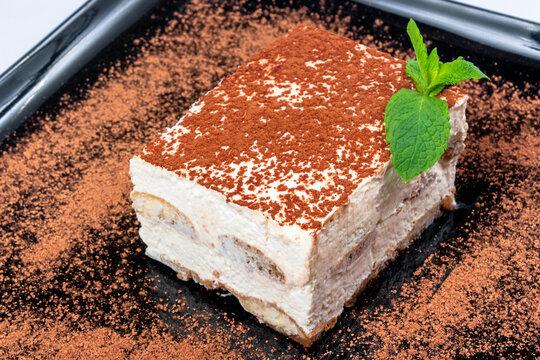 traditional rich tiramisu cake with cinnamon on a black plate. tasty italian dessert decorated with mint