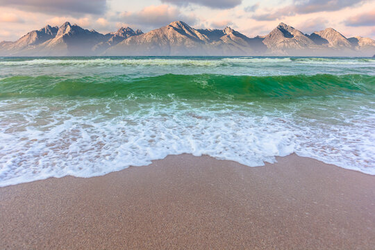 golden beach and green sea on a cloudy evening. beautiful view of waves rolling the coast beneath a glowing sky. cliff in the distance. composite image
