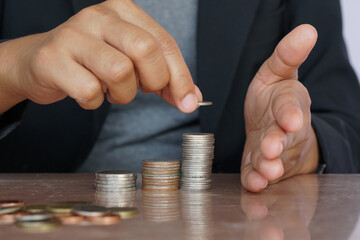 Businesswoman hand putting money coin stack. Creative ideas for saving money concept.