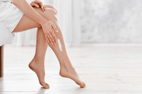 Woman applying moisturizer cream on her legs after shower