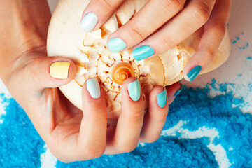 woman hands holding sea shell and sea salt with manicured nails