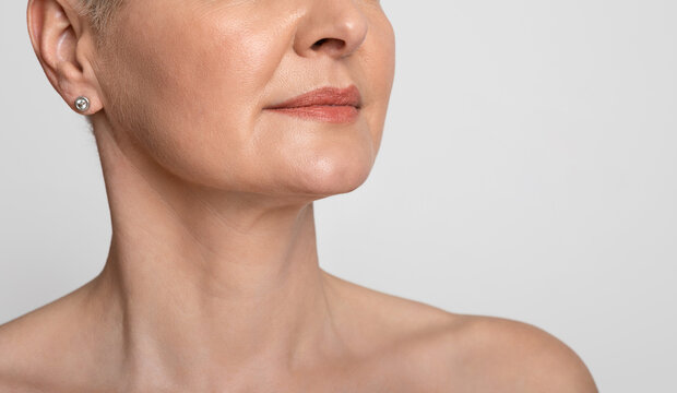 Skin Lifting. Mature woman with smooth skin over light background, cropped image