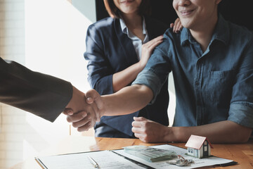 Young Asian Couple  shaking hands with Estate agent after contract signature. Real Estate concept.