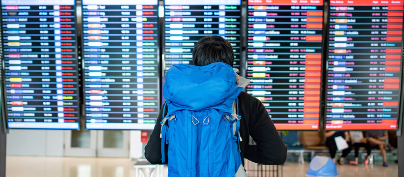 Vacation travel concept. Asian man backpacker and tourist carrying blue backpack checking flight information schedule on arrival departure board in international airport terminal.
