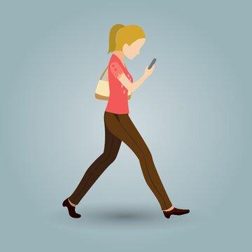 woman walking and looking at phone