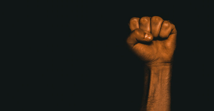 Male black fist on a black background. Aggressiveness, masculinity, the concept of challenge