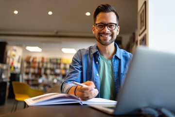 Smiling male student working and studying in a library