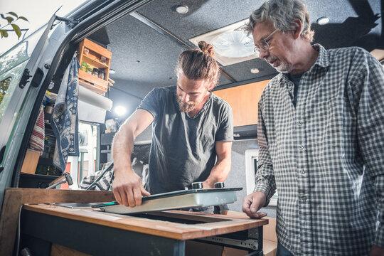 Two men installing a stove into a camper van