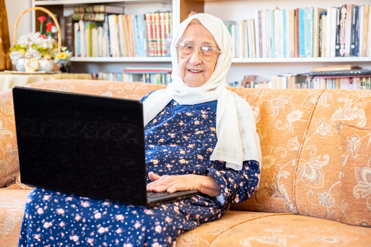 Happy old arabic muslim woamn using technology while sitting on couch