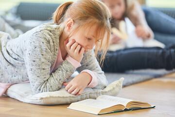 Blondes Mädchen liest konzentriert
