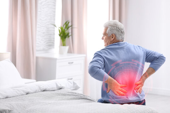 Senior man suffering from back pain after sleeping on uncomfortable mattress at home