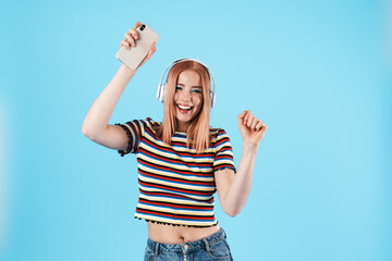 Image of girl dancing while using wireless headphones and cellphone
