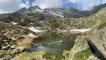 Small mountain lake in a wilderness alpine range. North Italy, Europe.