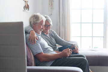 couple of seniors or mature people at home in the sofa looking and using their tablet or technology device smiling and laughing watching videos or funny photos - mobile and technology lifestyle