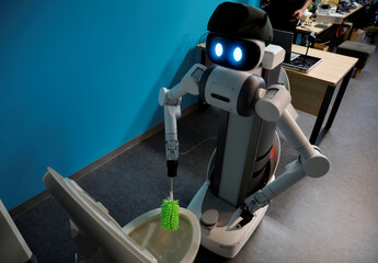 Mira Robotics' Ugo avatar robot cleans a toilet during a demonstration at the company's laboratory in Kawasaki