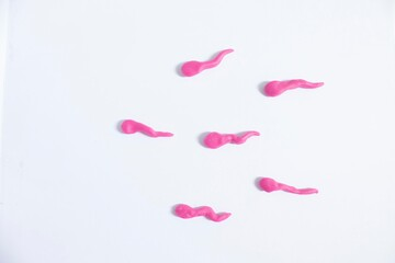 Pink sperm on white background. Play dough