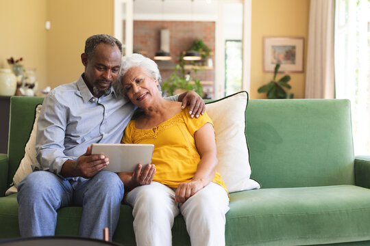 Senior African American couple using digital tablet in a canape