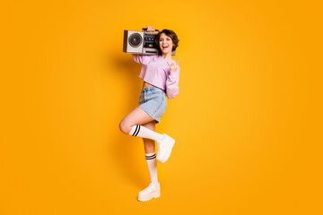 Full size photo of crazy funny teen want listen rock song music hold boom box enjoy rejoice show horned symbol wear pink white sweater jumper denim isolated over bright shine color background