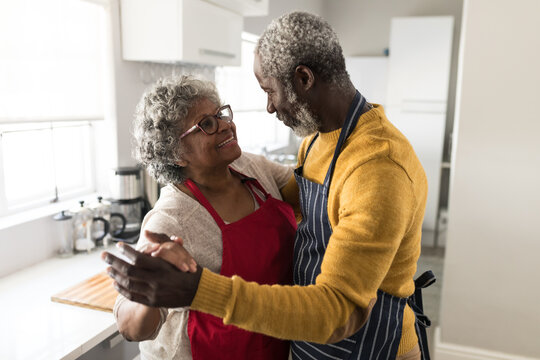 A senior African American couple dancing in the kitchen