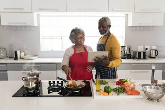 A senior African American couple cooking together