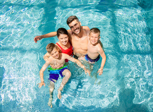 Top view of smiling family of four having fun and relaxing in indoor swimming pool at hotel resort.