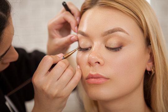 Unrecognizable makeup artist applying eyeshadow on eyelids of a beautiful woman