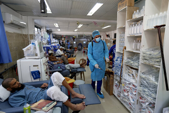 A Palestinian cleaner sanitizes a renal unit as patients undergo dialysis treatment in a hospital amid COVDI-19 crisis, in the southern Gaza Strip