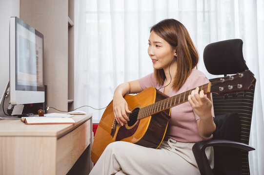 Asian woman guitar player and vlogger playing guitar in front computer at home while social distancing of coronavirus outbreak, online guitar lesson,livestream on social media concept.
