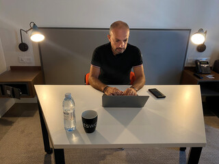 A man works on his laptop in a bedroom-turned-office at a hotel which is offering private working spaces away from home, following the outbreak of coronavirus disease (COVID-19), in Dubai
